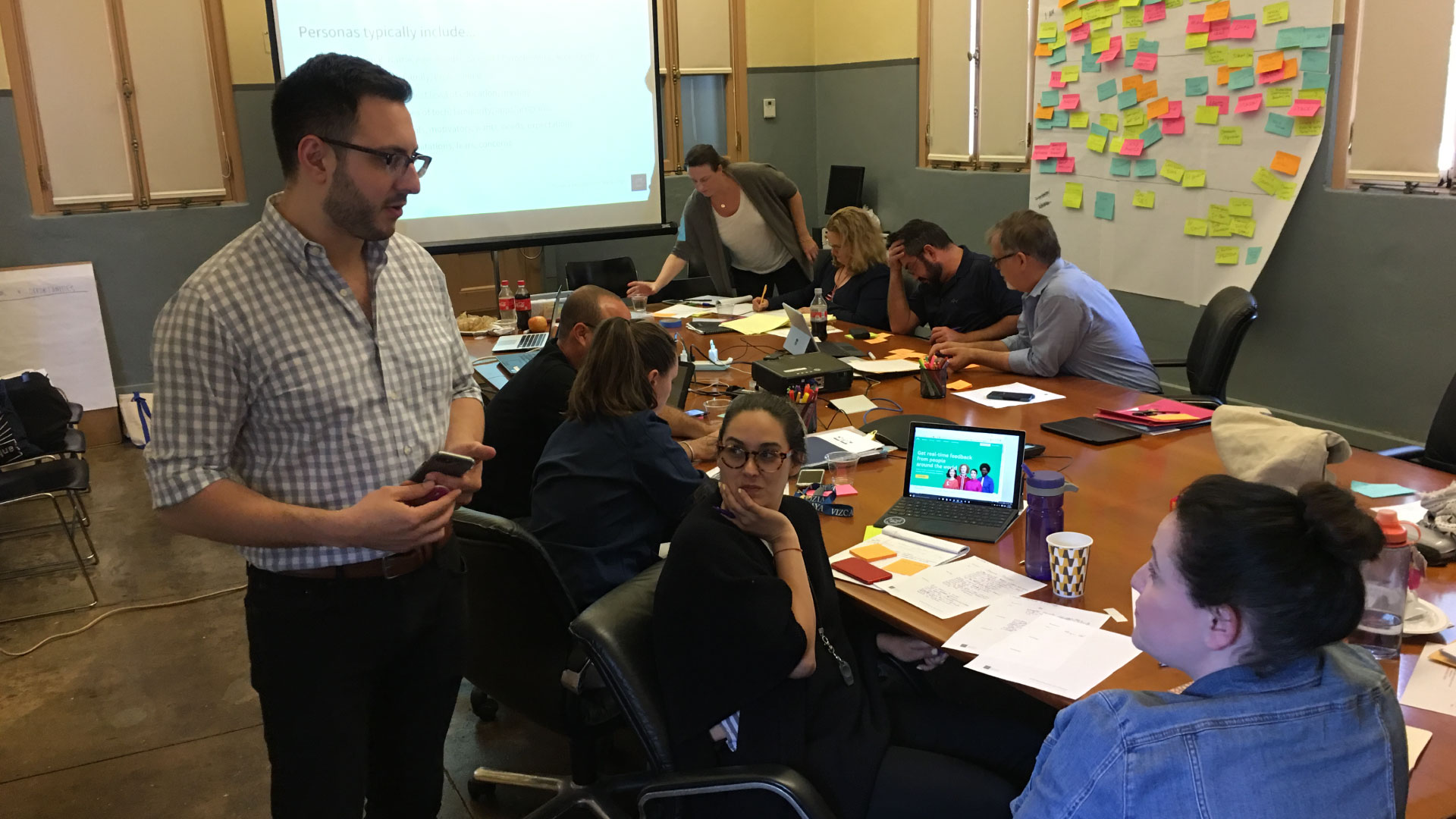Michael Tedeschi facilitating a design thinking workshop with participants around a table with sticky notes in the background.